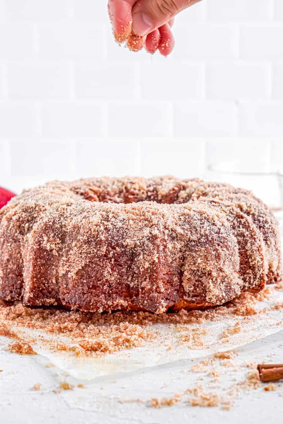 Sprinkling cinnamon sugar over the entire apple cider doughnut cake