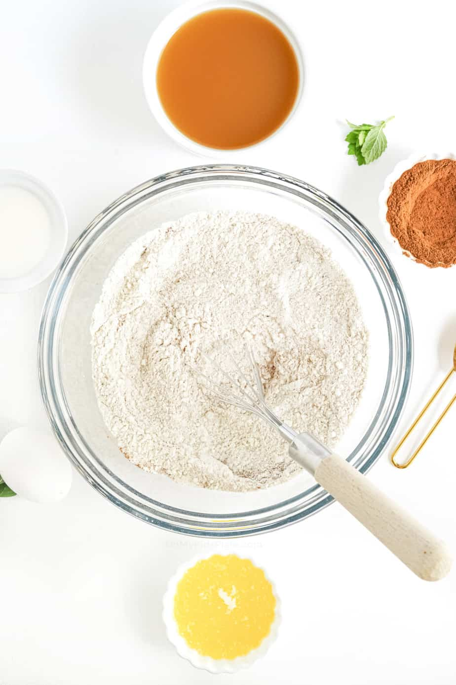 Mixing dry ingredients for doughnut batter from overhead with apple cider, cinnamon and melted butter in bowls nearby.