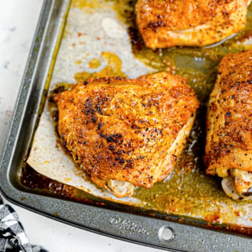 Golden brown baked chicken thighs sitting in juices on the pan close up