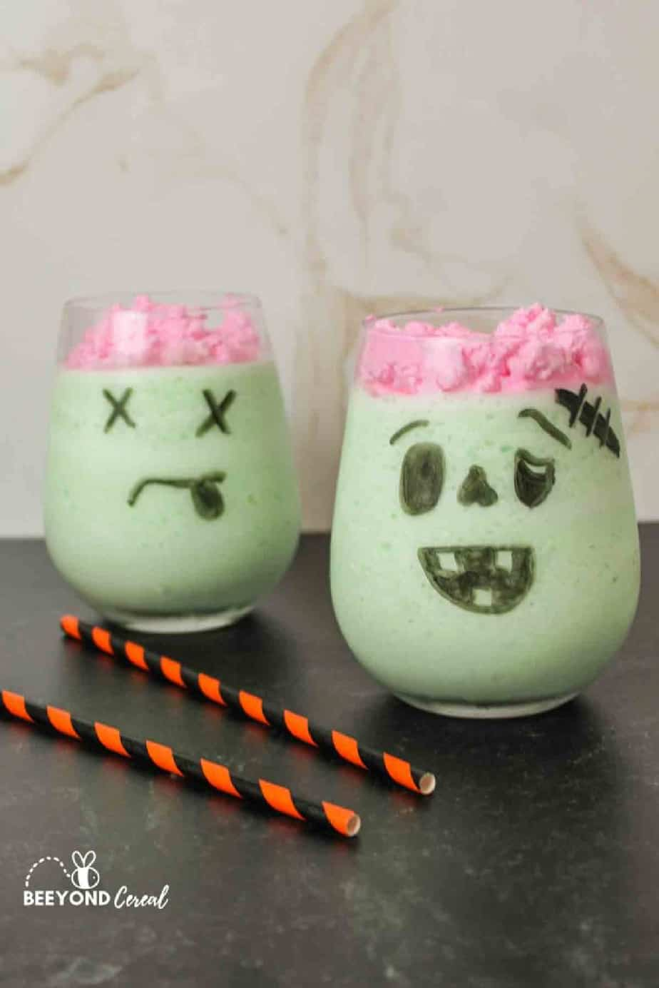 Green monster shaped drink with pink whipped cream to look like brains.