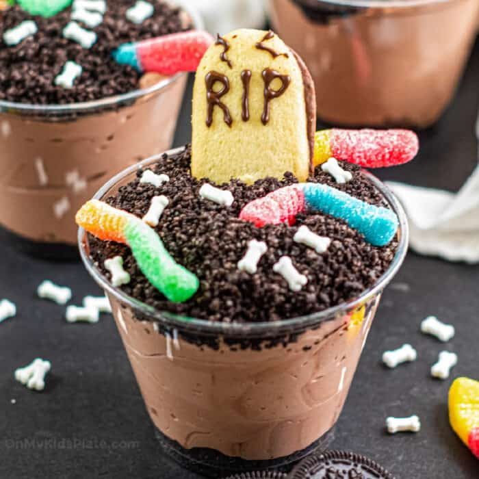 Close up of a chocolate dirt pudding cup decorated with gummy worms, bone sprinkles and a cookie headstone.