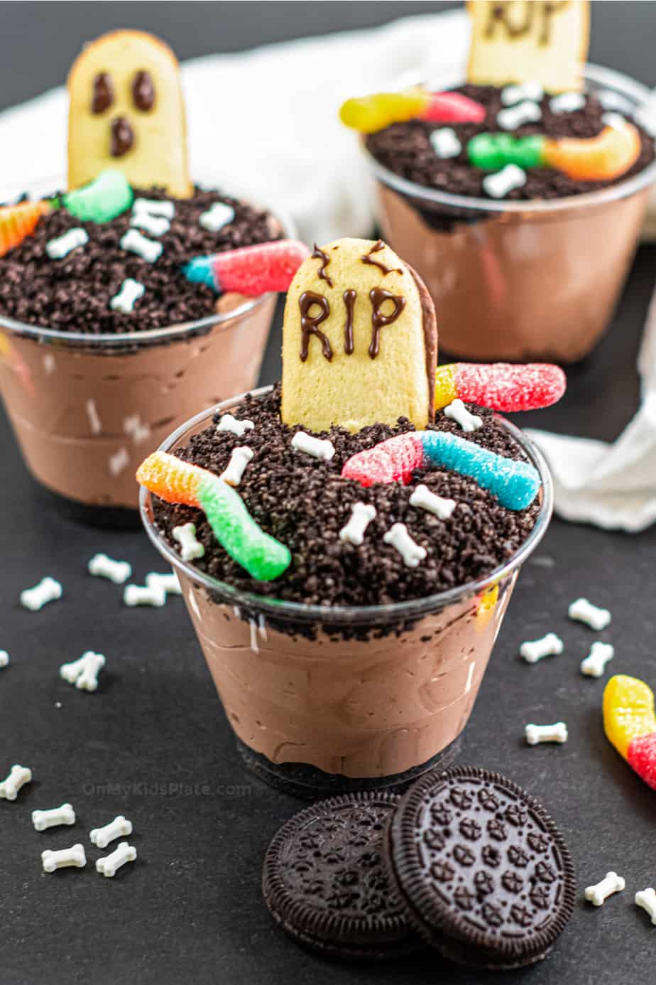 Three clear cups filled with pudding, topped with Oreo crumbs and tombstone and ghost shaped cookies.
