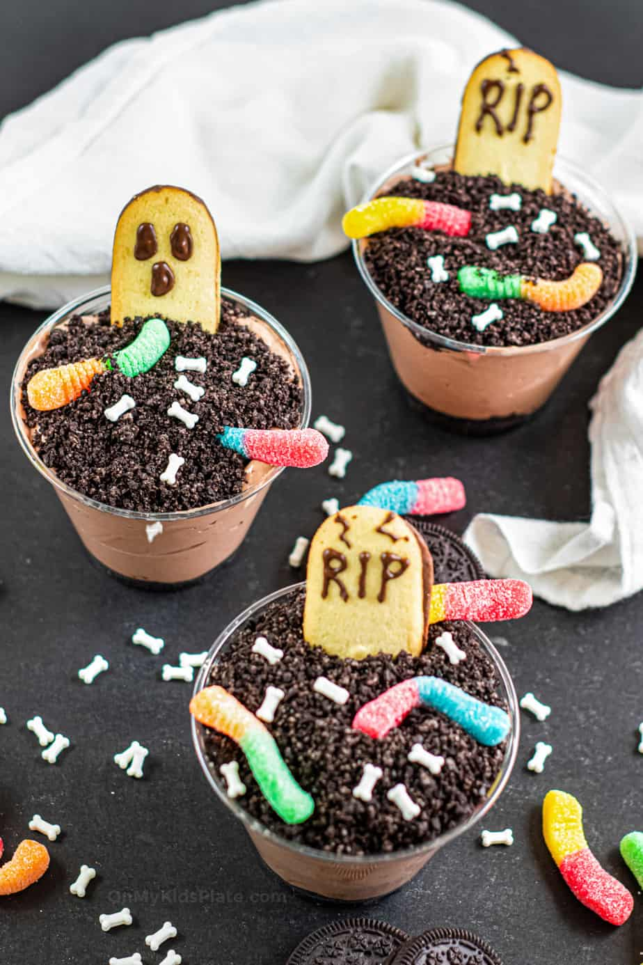 Three finished Graveyard dirt pudding cups topped with headstones, ghosts, gummy worms and bone candy sprinkles.