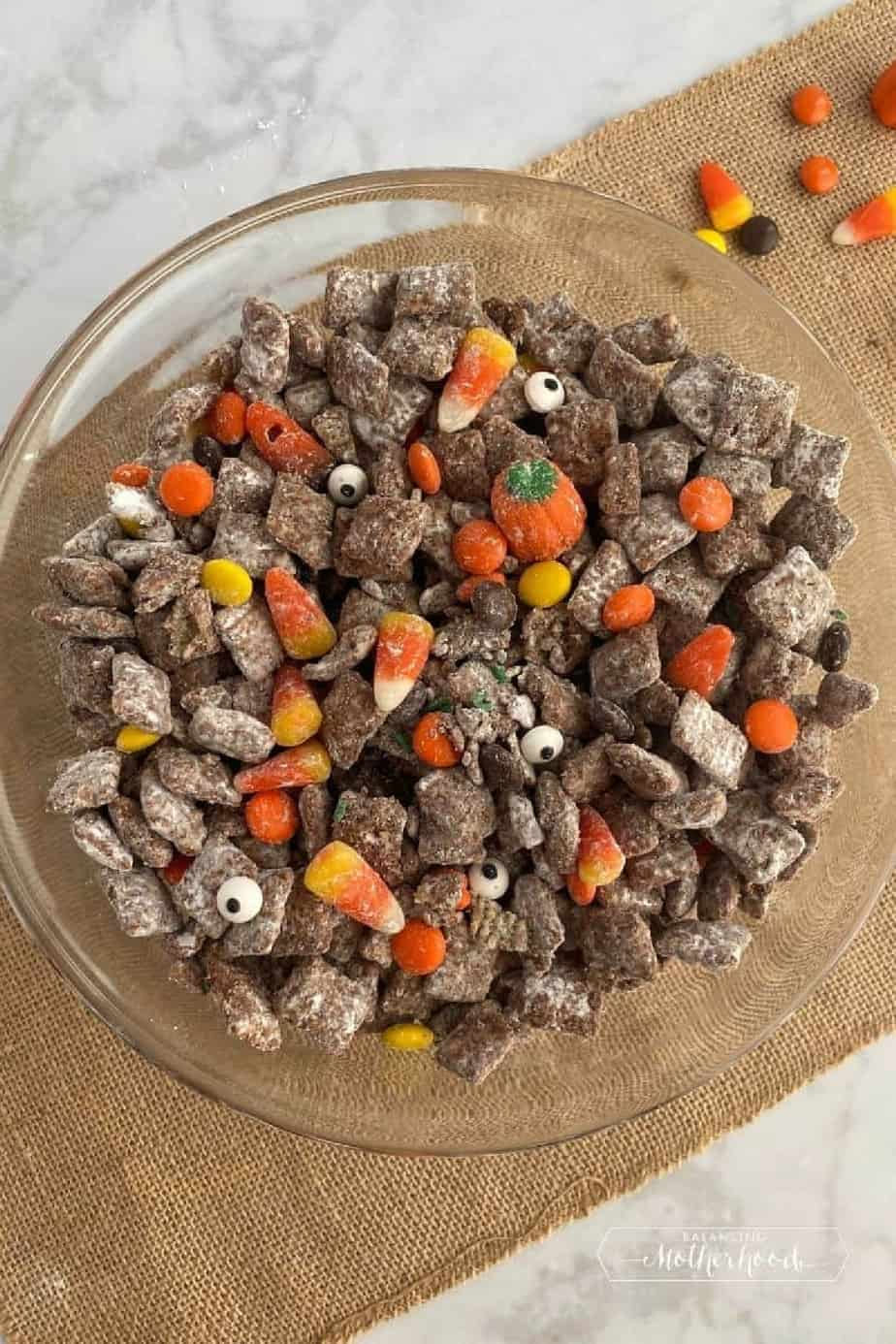 A large bowl from overhead fully of chocolate peanut butter covered cereal also known as muddy buddies, candy corn and candy pumpkins