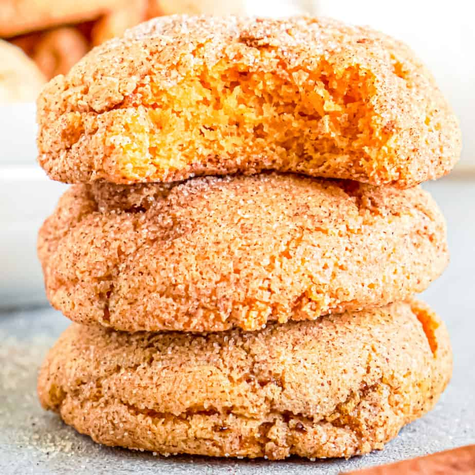 Pumpkin snickerdoodle cookies stacked with a bite out of the top cookie close up