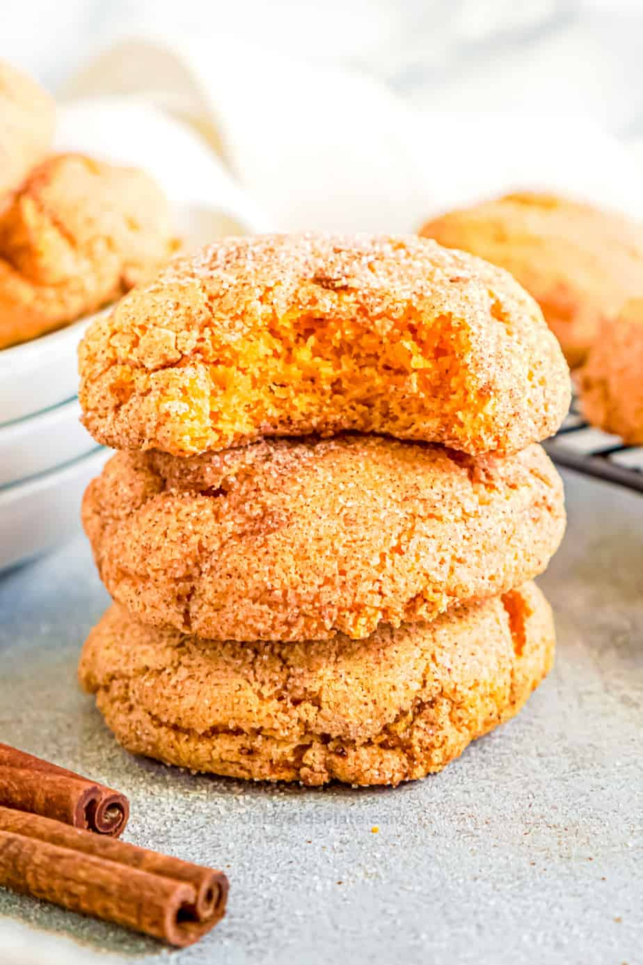 pumpkin snickerdoodle cookies stacked with a bite taken from the top cookie