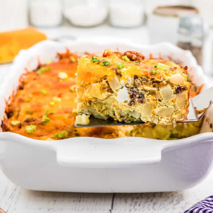 Slice of breakfast casserole being lifted from the pan with a spatula from the side.
