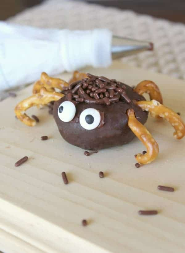 Store-bought donut decorated with pretzel legs, candy eyes and sprinkles to look like a spider