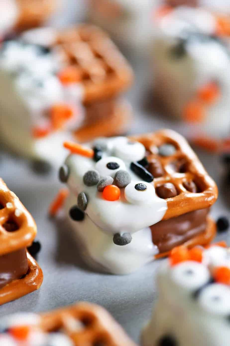 Square pretzels with a candy bar melted in between and dipped in chocolate and decorated with halloween sprinkes
