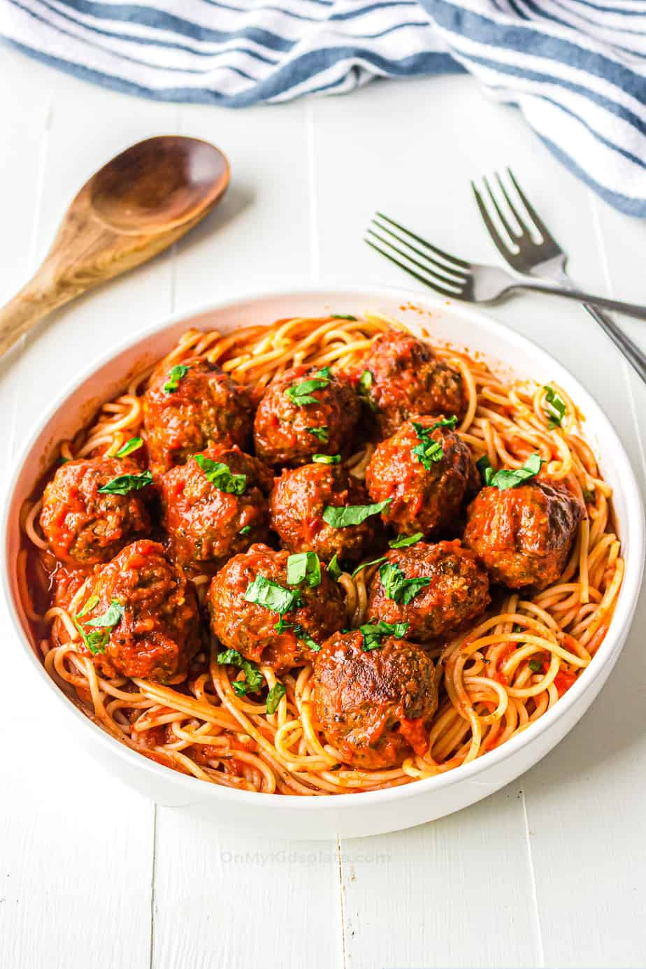 Meatballs in a large bowl over top of spaghetti with marinara sauce.