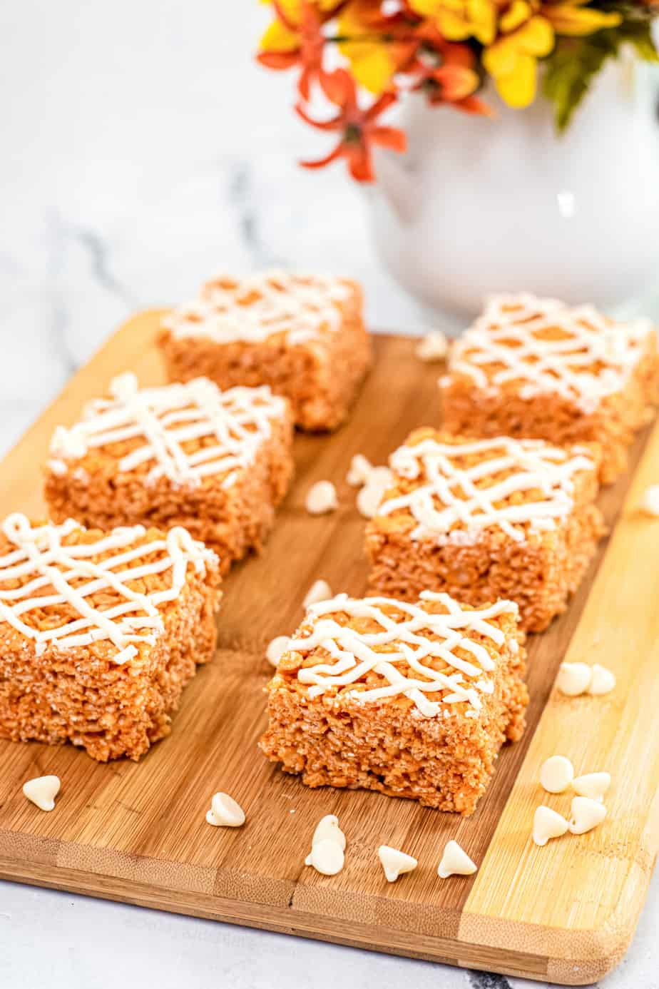 Pumpkin rice krispie treats sliced into squares on a cutting board with a white chocolate drizzle on top and white chocolate chips scattered on the cutting board.