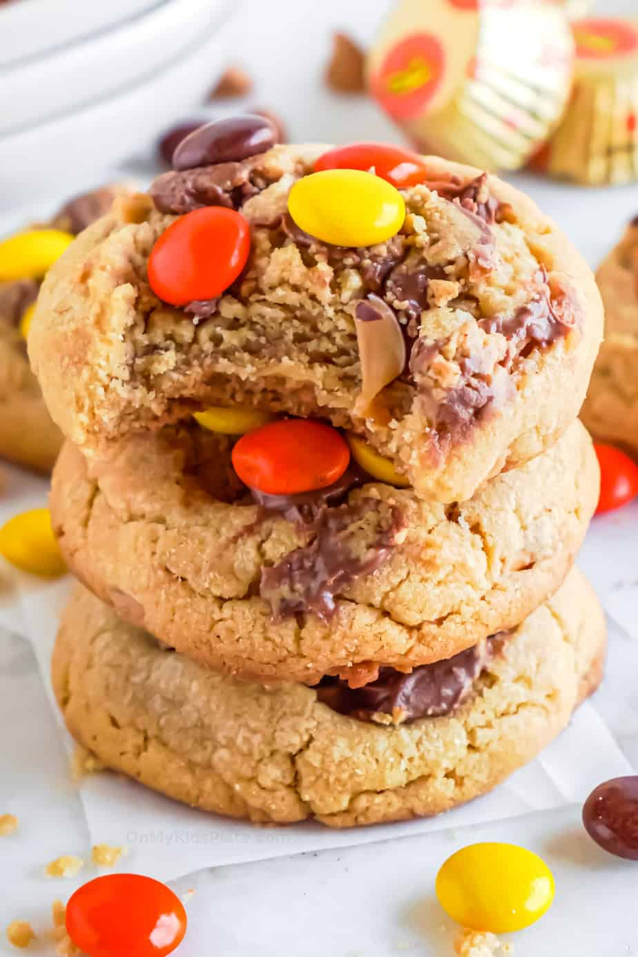 Stack of cookies topped with Reese's pieces and peanut butter cup pieces. The top cookie has a bite missing