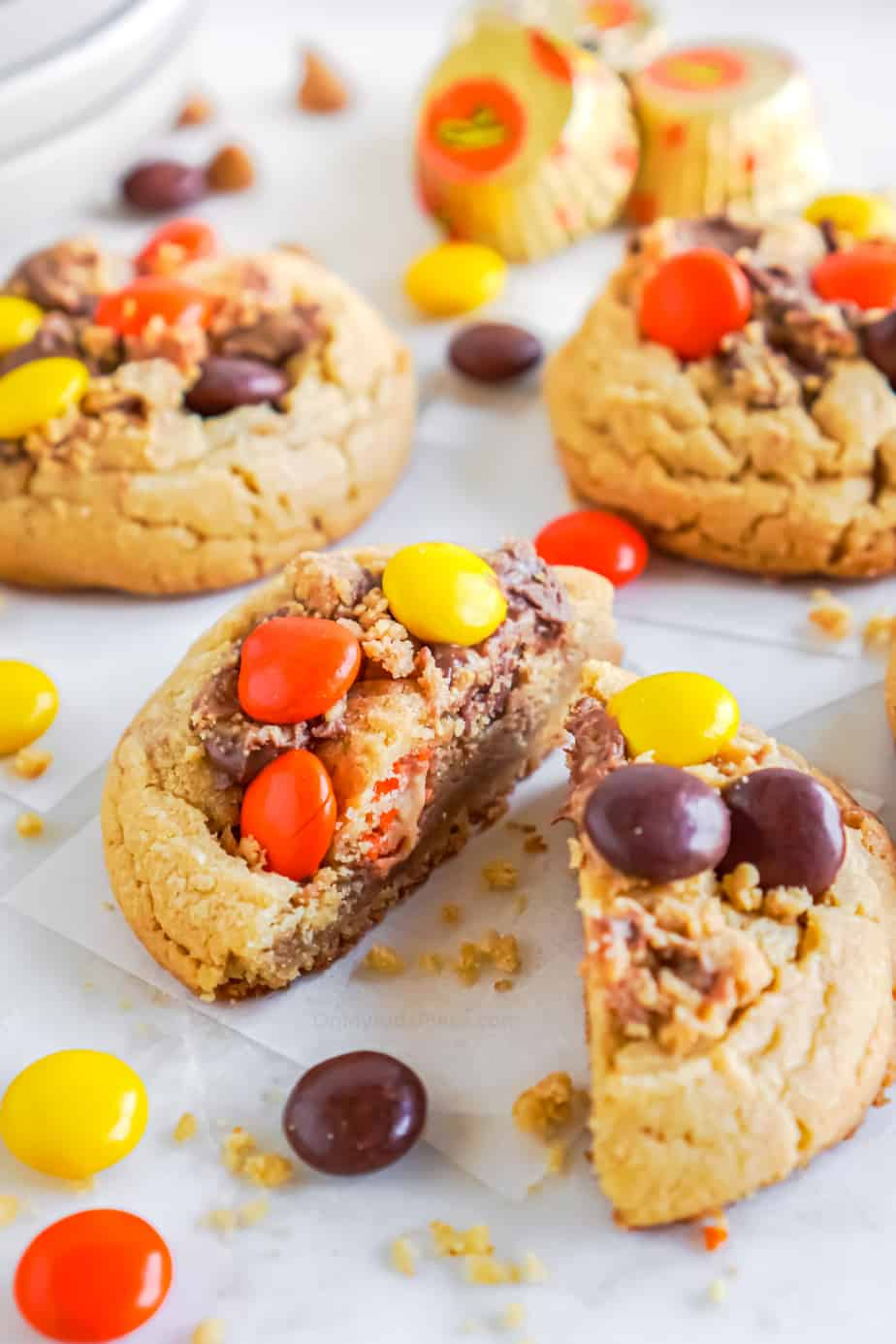 Cookie slices in half to see the inside up close covered in peanut butter candies and pieces of peanut butter cups