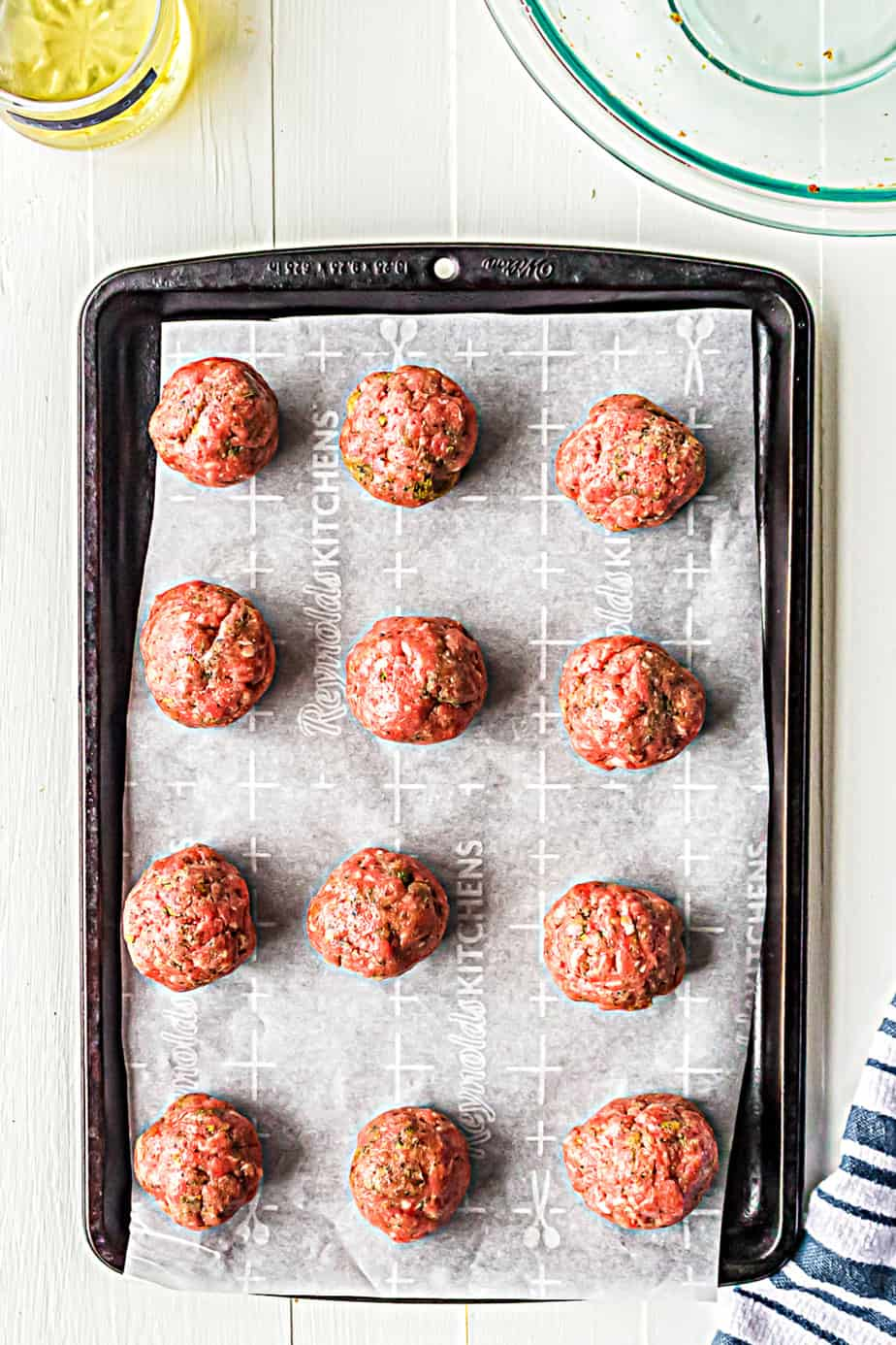 Overhead look at twelve raw meatballs on a baking pan lined with parchment paper.