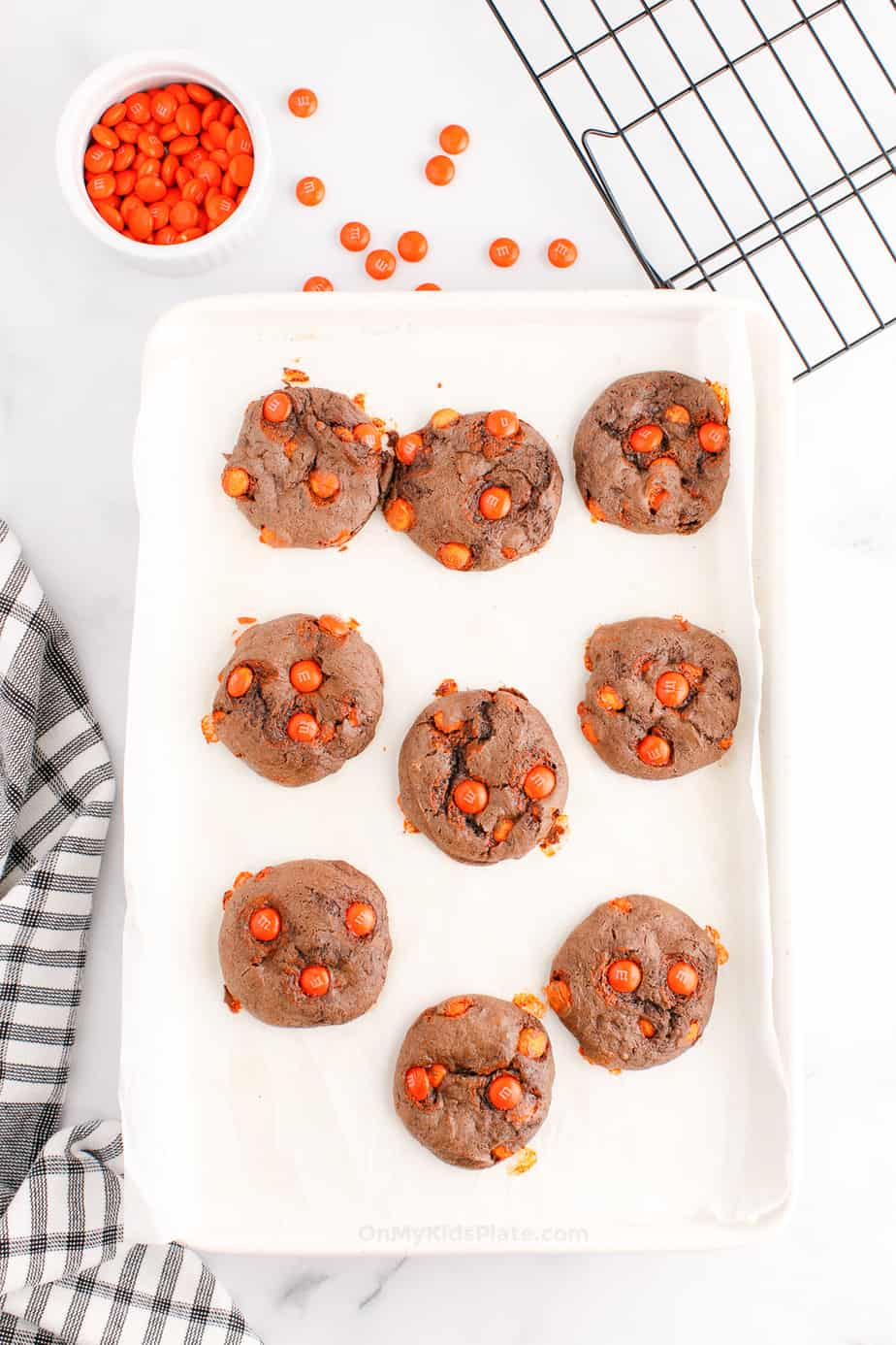 Chocolate cookies with orange candies baked on a pan with a wire rack and more orange candies in a bowl next to the pan