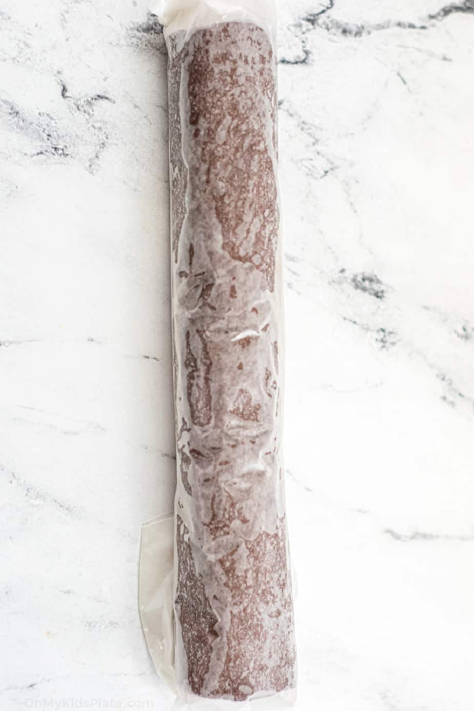 Chocolate cookie dough rolled into a long log and wrapped in parchment paper.