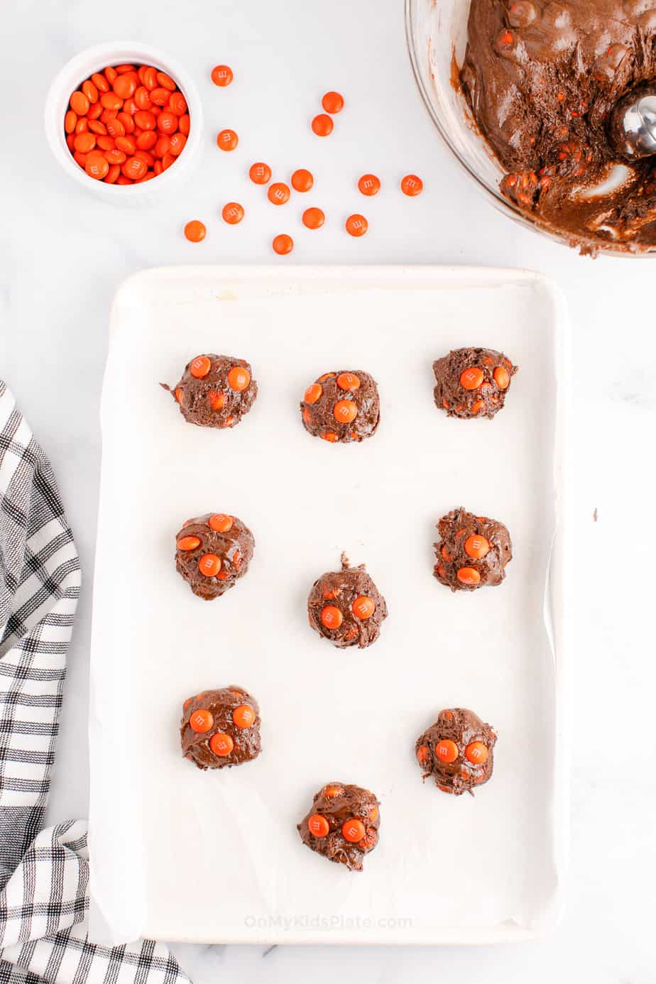 Cookie dough spaced evenly on a pan with more orange candies and chocolate cookie dough in bowls in the top.