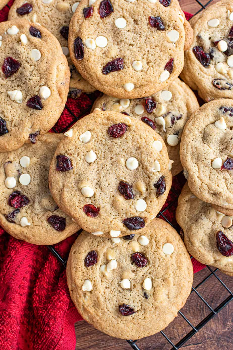 White chocolate chip and cranberry cookies stacked on a wire rack form overhead.