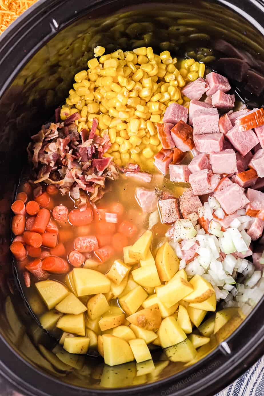 Diced potatoes, ham, bacon, carrots, onions and corn in a broth in a slowcooker pot.