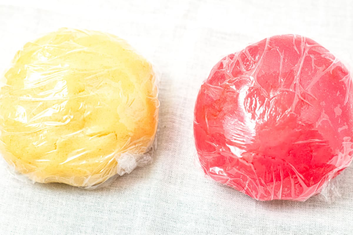 White and red cookie dough balls wrapped in plastic wrap
