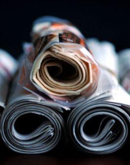 Tortilloja rullalle käärittyinä paketissaan rullattujen sanomalehtien päällä.