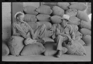 Two farmers sitting on bags of rice in Abbeville, Louisiana, September, 1938. Photo by Leo Russell from the Library of Congress Prints and Photographs Division.