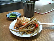 A dish containing a Japanese appetizer, kinpira gobō, consisting of sautéed burdock root and carrot, with a side of sautéed dried daikon. Photo courtesy of Wikipedia