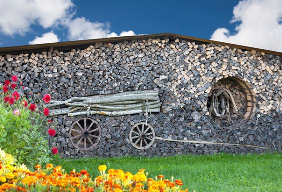 Stacked firewood art. Piled wood, grass and flowers.