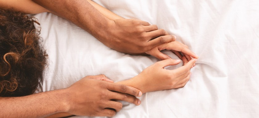 Close-up of someone pinning their partners hands above their head while having sex. Photo.