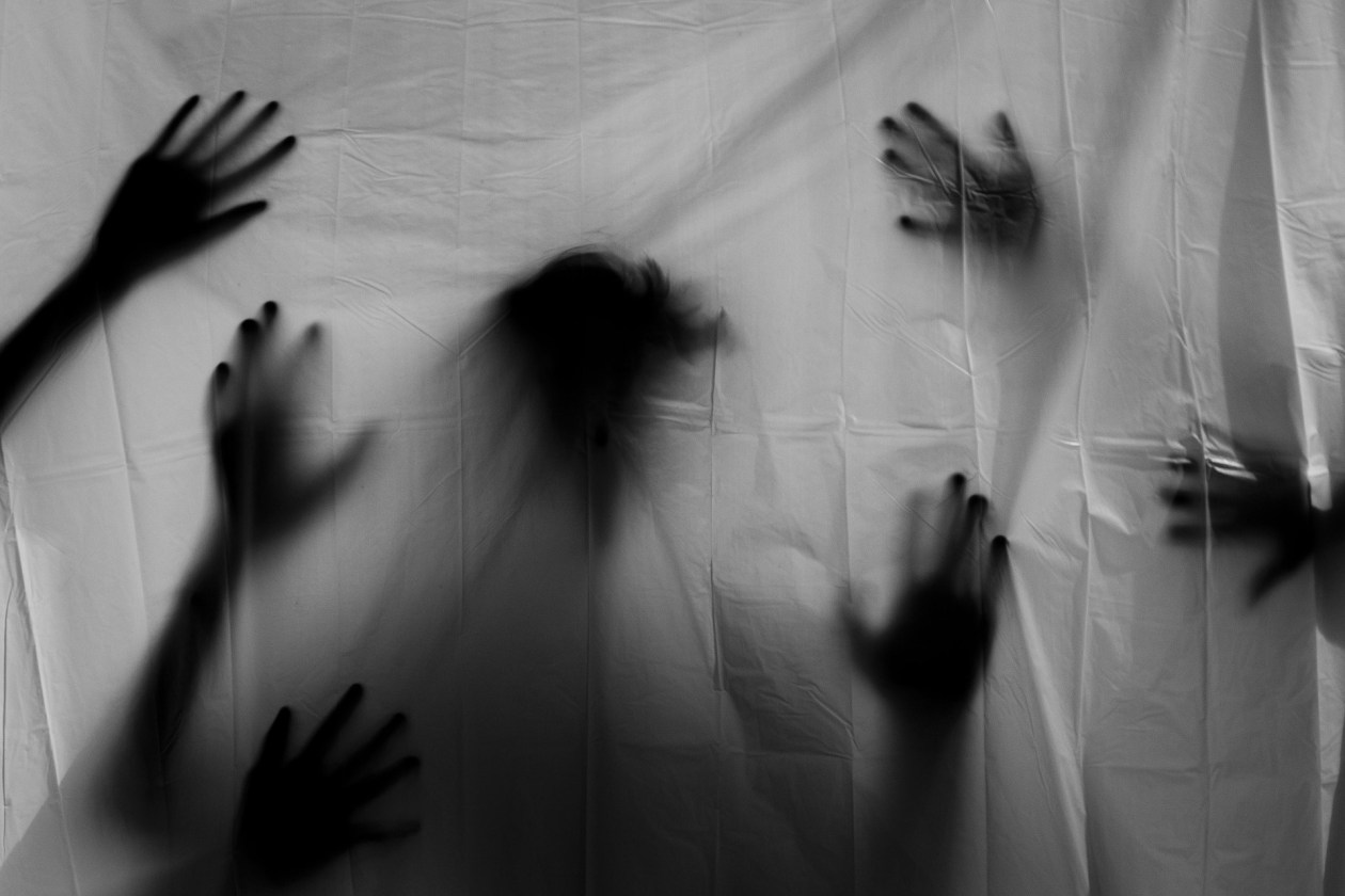 A sheet obscures several ghost-like hands seen only as shadows. Photo.