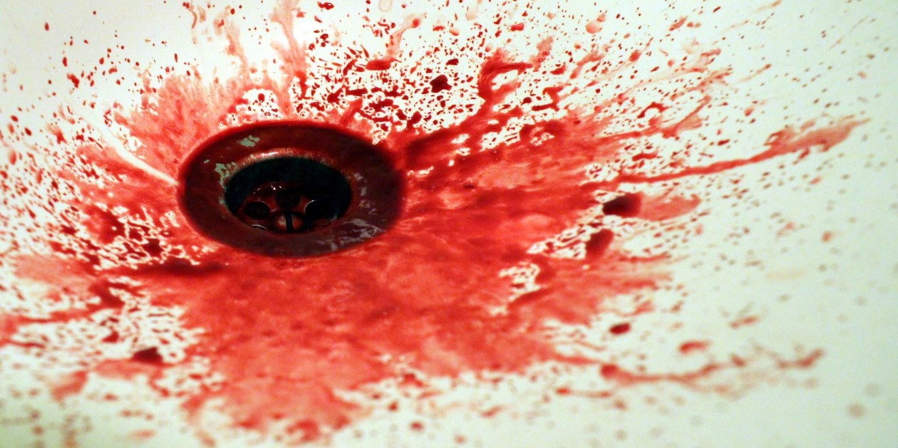 A shower drain with blood splashed around it. Photo.
