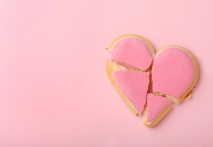 Broken heart shaped cookie on pink background. Photo.
