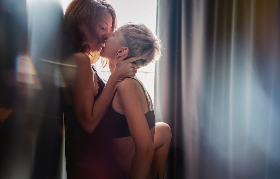 Two young queer women kiss passionately in their underwear. Photo.