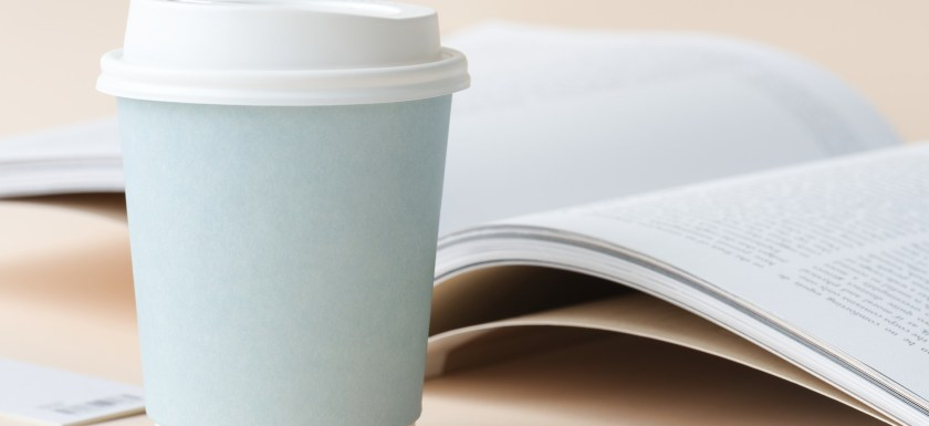 A blue take-away coffee cup and a magazine. Photo.