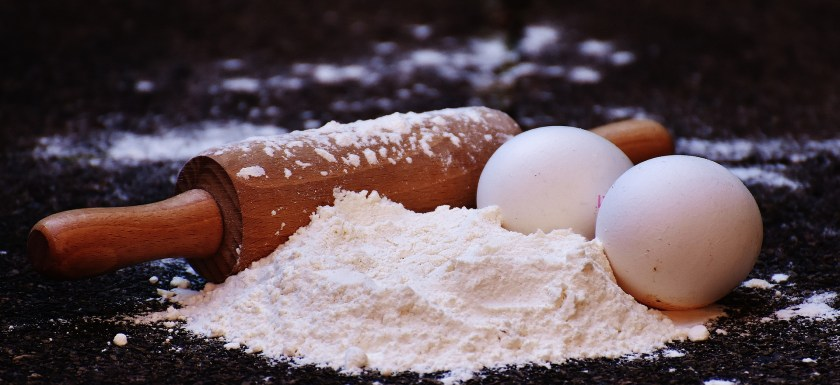 Baking ingredients, with flour covering eggs and a rolling pin. Photo.