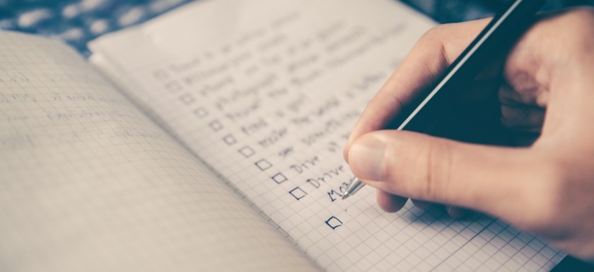 An open notebook with a hand holding a pen and adding new items to a checklist.