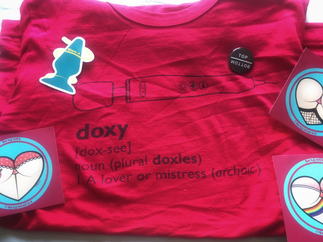 Bright pink Doxy wand t-shirt with other sex positive stickers and badges scattered on it. Photo.