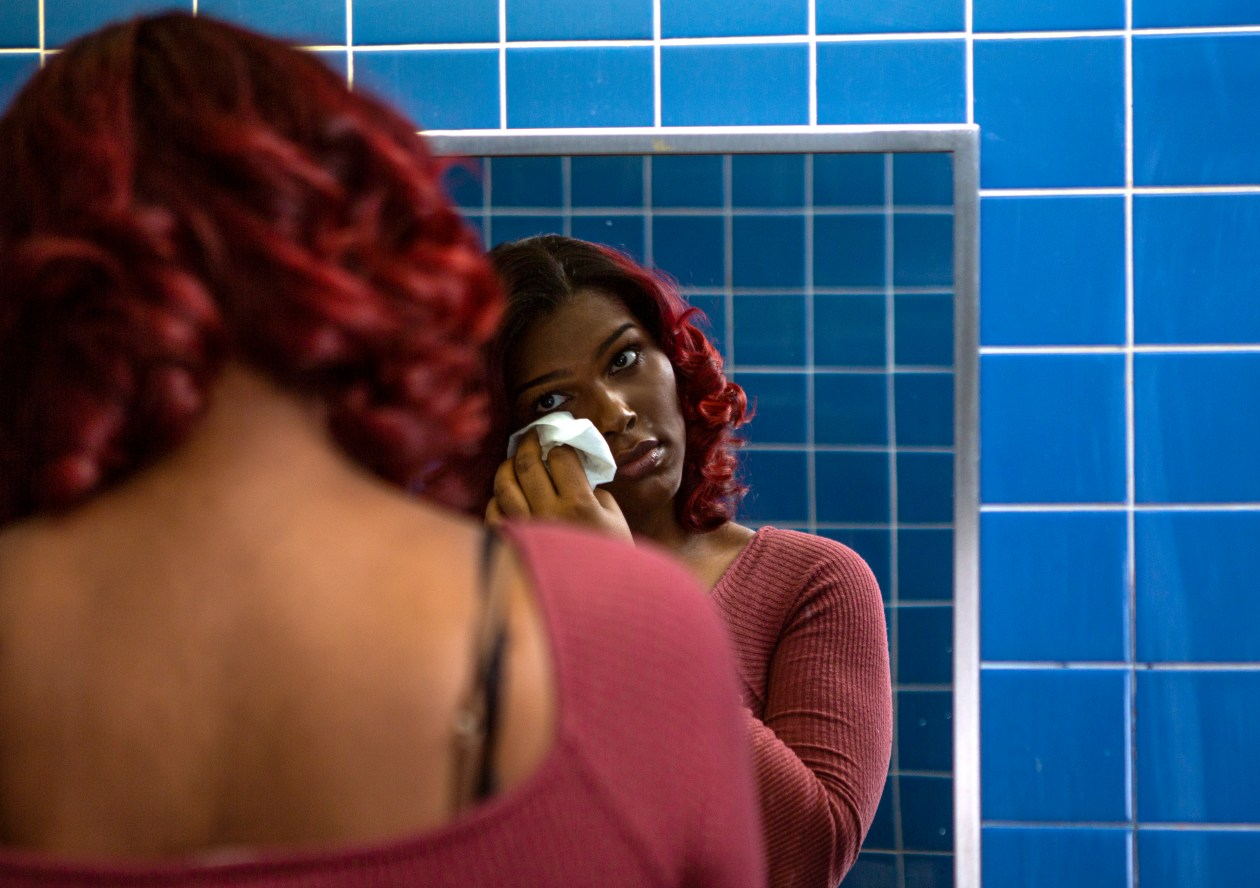 A transgender woman wipes tears off her face in a bathroom.