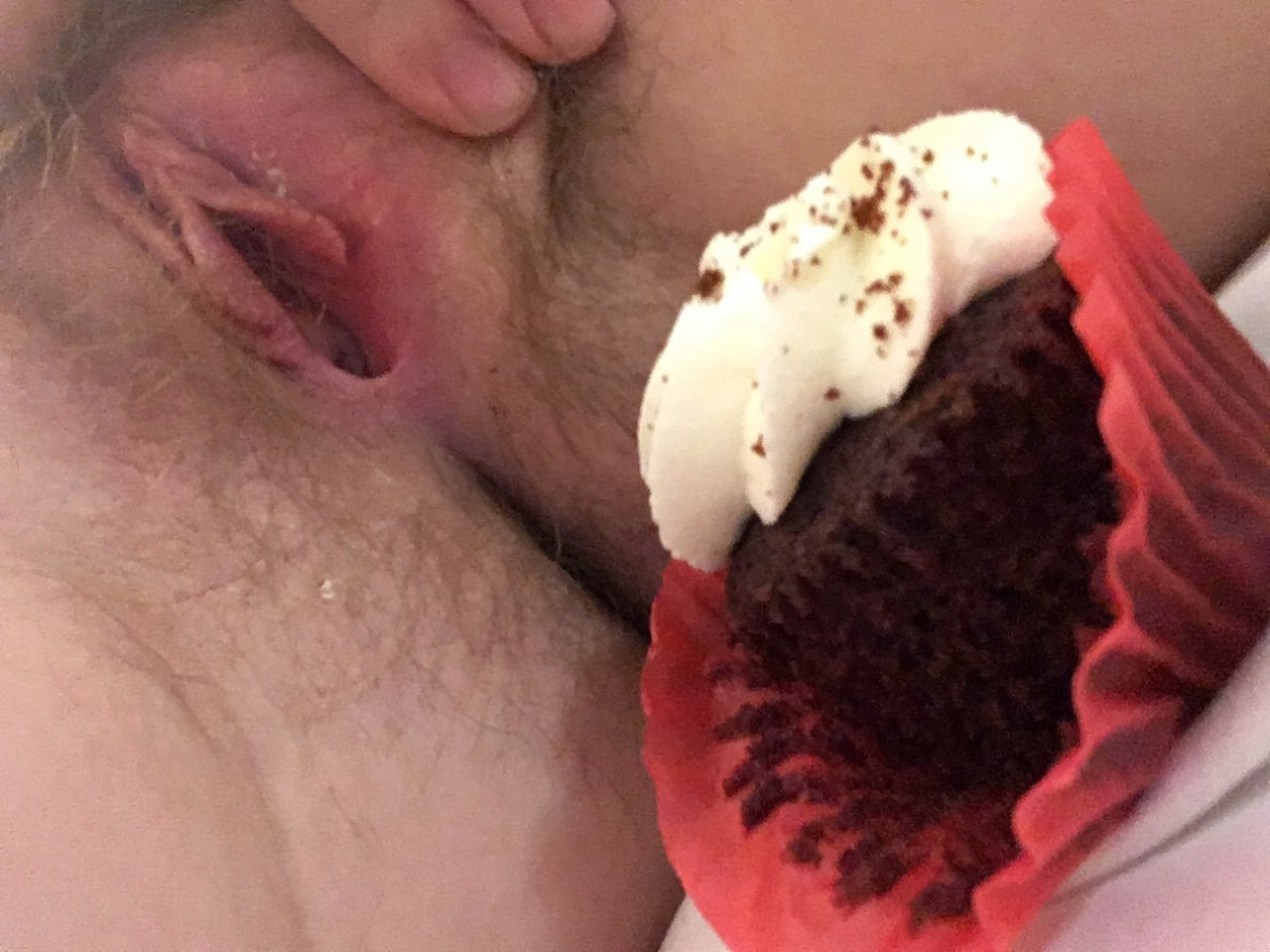 A red velvet cupcake sits in front of a spread-open vulva. Photo.