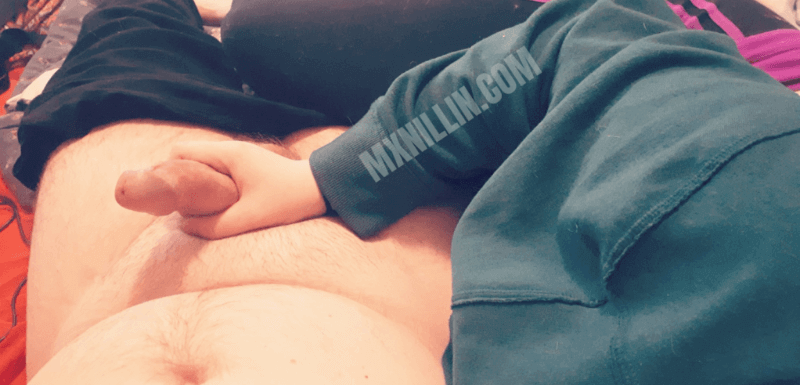One person lies naked with their cock hard, and another is curled into them and gripping the base of their partner's cock. Photo.