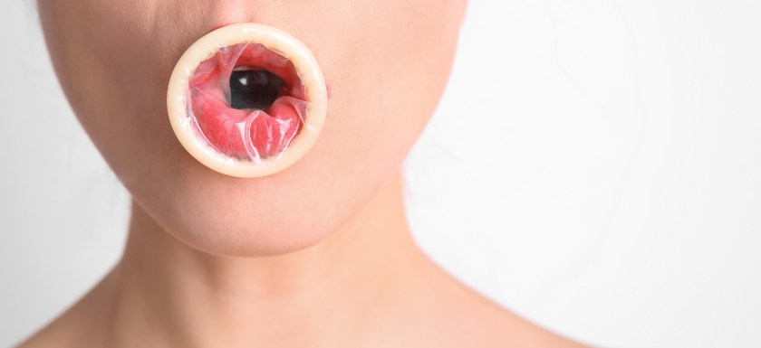 Sexy young woman with condom in her mouth on light background. Photo.