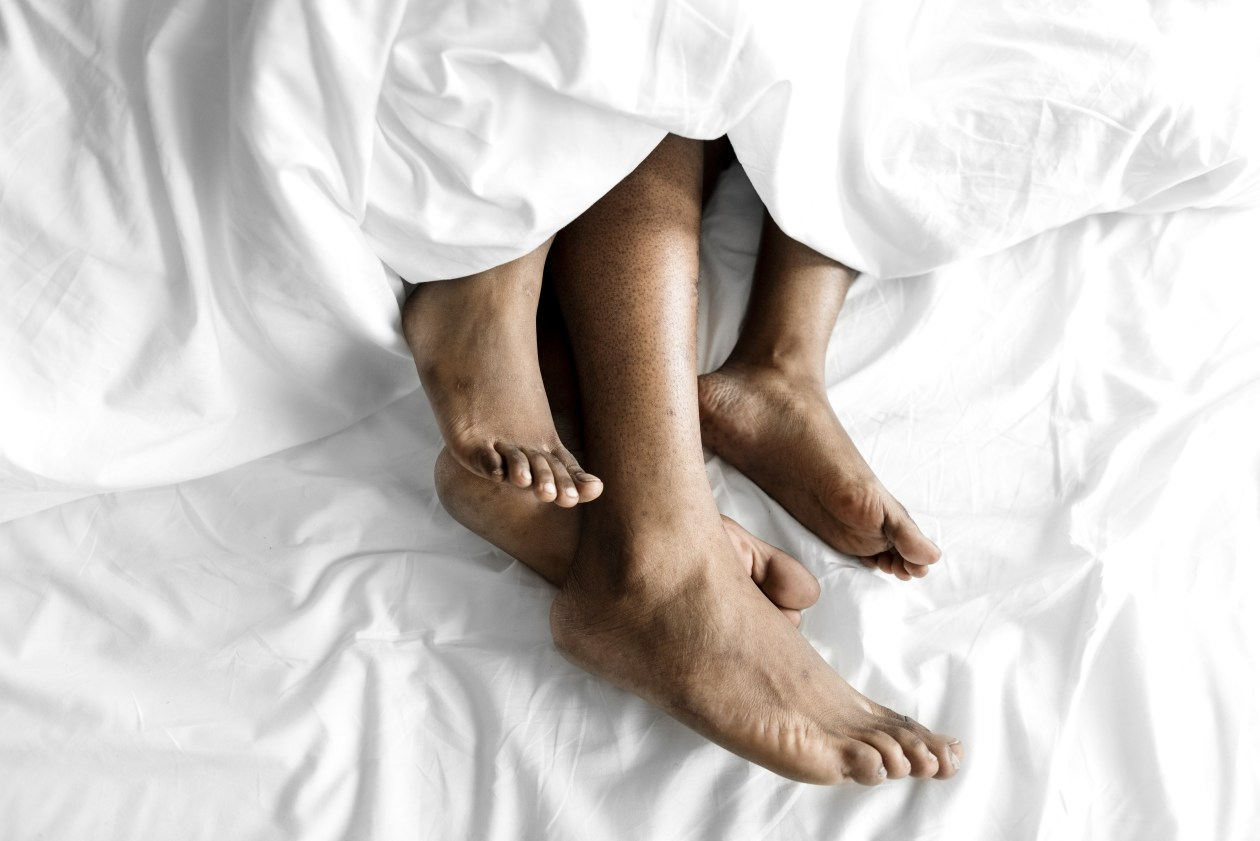 Two sets of feet emerge from the bottom of a duvet. Photo.