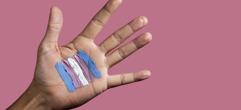 Closeup of the palm of the hand of a young caucasian person with a transgender flag painted on it, against a pink background. Photo.