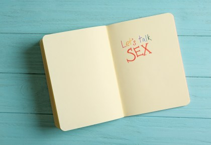 "Notebook with phrase ""LET'S TALK SEX"" on light blue wooden background. Photo."