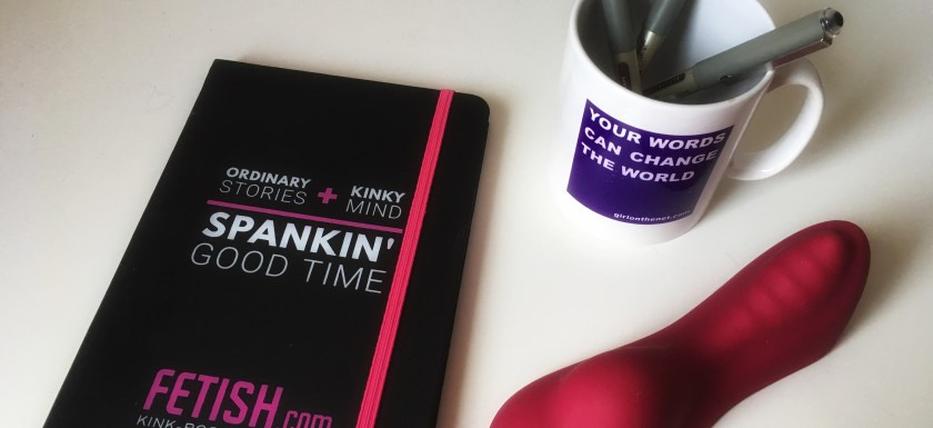 A sex blogging notebook, mug full of pens, and pink sex toy sit on a white desk. Photo.