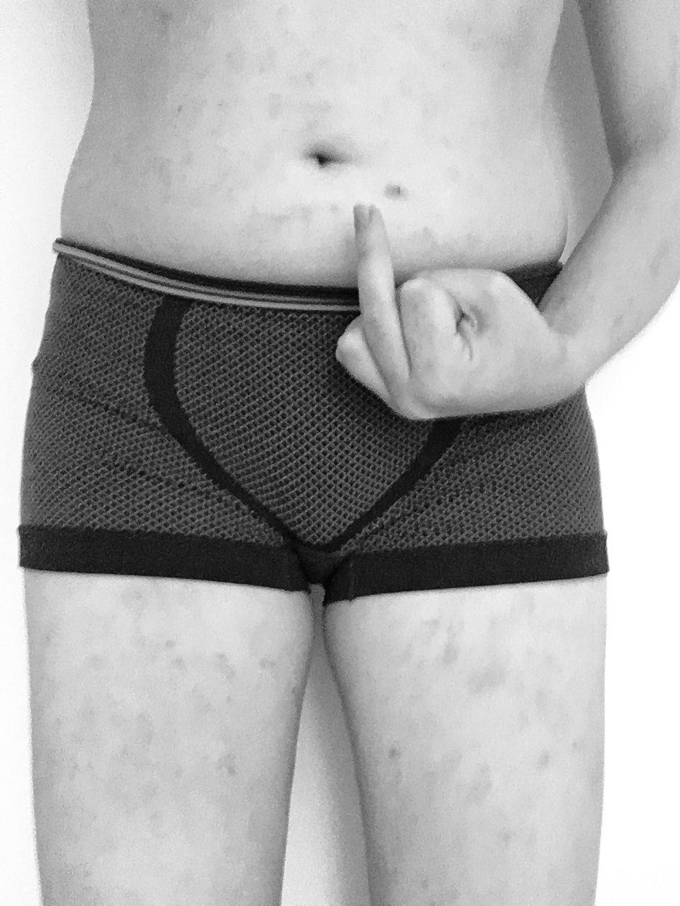 A black and white image of a girl in boxers sticking her middle finger up to the camera. Photo.