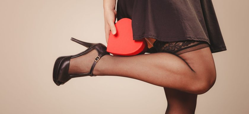 A woman in stockings and high heels holds a heart-shaped red gift box against her calf. Photo.