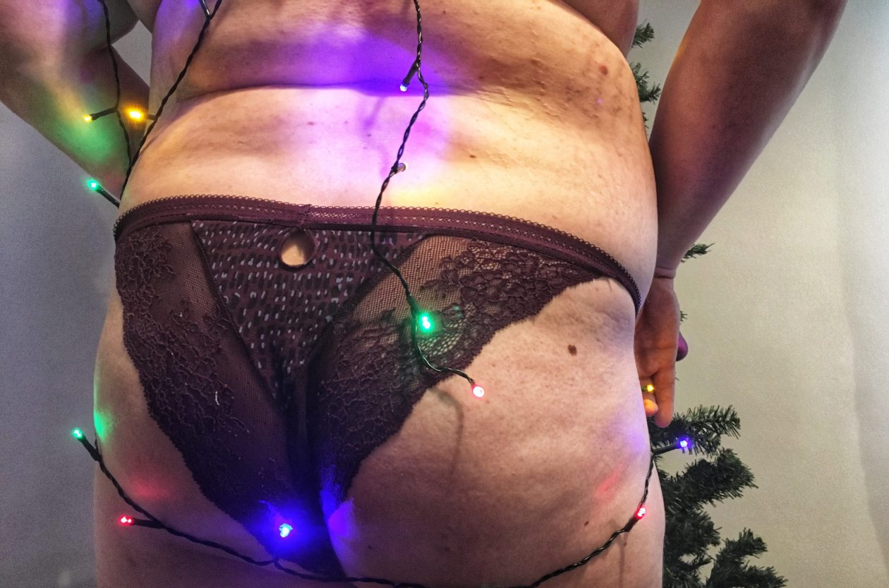 An enby wearing purple lace panties bares their ass in front of a Christmas tree. Photo.