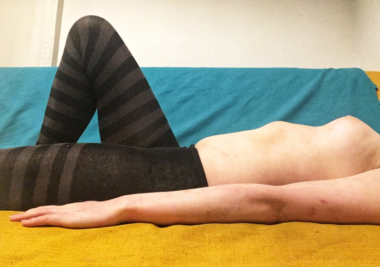 A woman lies on her back on the sofa, wearing stripy black and grey tights. Photo.