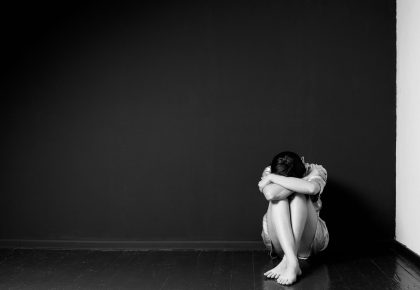 Sad woman sitting in the corner of a room, head on the knees, face is hidden. Photo.